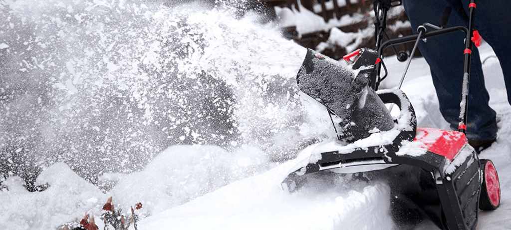 This is an image of a man snow blowing